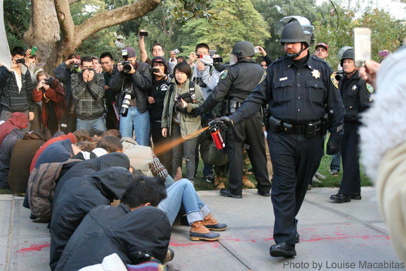 Louise Macabitas: Photo of Police Officer Pepper Spraying UC Davis Students